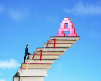 Businessman climbing books stairs toward alphabet A shape blocks Stock Photos