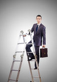Businessman climbing career ladder against Stock Photos