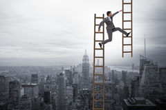 The businessman climbing career ladder in business concept Stock Photos
