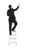 Businessman climbing career ladder Stock Image