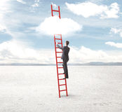 Businessman climbing on clouds Royalty Free Stock Images
