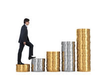 Businessman climbing on coins Stock Images