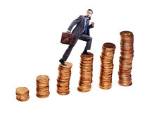 Businessman climbing coins stacks Royalty Free Stock Image