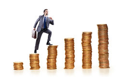 Businessman climbing coins stacks Stock Images