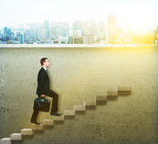 Businessman climbing concrete ladder Royalty Free Stock Photo