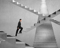 Businessman climbing on concrete stair maze Royalty Free Stock Photo