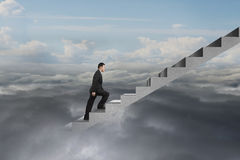 Businessman climbing on concrete stairs with natural cloudy sky. Cloudscape background Stock Photos