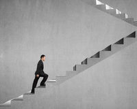 Businessman climbing on concrete stairs Stock Images