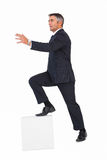 Businessman climbing on a cube with arms out Royalty Free Stock Image