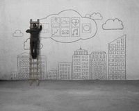 Businessman climbing and drawing app icon with sky buildings doo Stock Photos