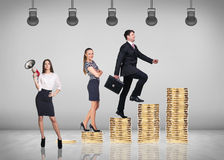 Businessman climbing gold coins stacks Royalty Free Stock Photo