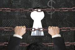 Businessman climbing on iron chain for keyhole with city buildin Royalty Free Stock Photography