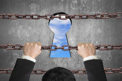 Businessman climbing on iron chain for keyhole with sky clouds Royalty Free Stock Image
