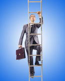 Businessman climbing the ladder against the Stock Photos