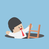 Businessman climbing a ladder out from a hole Royalty Free Stock Photography