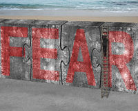 Businessman climbing ladder puzzles concrete wall red fear word Stock Photos
