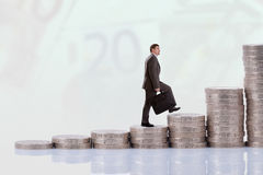 Businessman climbing money stairs Royalty Free Stock Photo