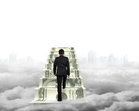 Businessman climbing the money stairs with gray cityscape clouds Royalty Free Stock Images