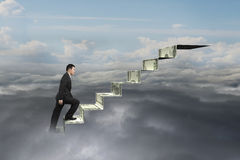 Businessman climbing on money stairs with natural sky cloudscape Stock Photos