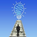Businessman climbing the money stairs toward light bulb Stock Photos