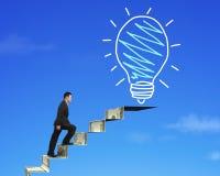 Businessman climbing the money stairs toward light bulb Royalty Free Stock Image