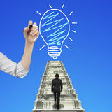 Businessman climbing money stairs toward light bulb hand drawing Stock Photo