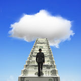 Businessman climbing the money stairs toward white cloud. In blue sky background stock photos