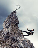 Businessman climbing mountain. With question sigh on top Royalty Free Stock Photography