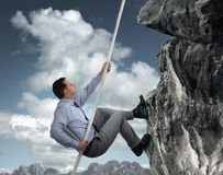 Businessman climbing mountain stock images