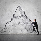 Businessman climbing a mountain Stock Photography