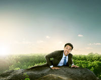 Businessman climbing mountain high Stock Images