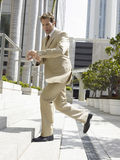 Businessman Climbing Office Steps While Looking At Wristwatch Stock Photo