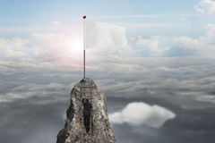 Businessman climbing on peak with blank flag and sunlight clouds Stock Photography