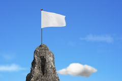 Businessman climbing on peak with blank white flag and sky Royalty Free Stock Images