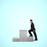 Businessman climbing on podium Stock Photo