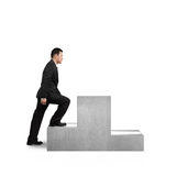 Businessman climbing on podium Stock Photos