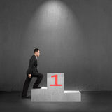Businessman climbing on podium with spot light, interior Stock Photo