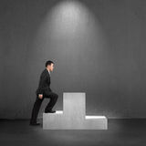 Businessman climbing on podium with spot lighting Stock Photo
