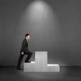 Businessman climbing on podium with spot lighting Stock Photo