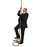 Businessman climbing rope Royalty Free Stock Photo