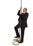 Businessman climbing rope Royalty Free Stock Photo