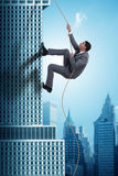 The businessman climbing skyscraper in challenge concept. Businessman climbing skyscraper in challenge concept Stock Photography