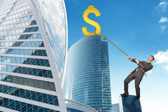 Businessman climbing skyscraper with dollar sign Royalty Free Stock Photography
