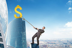 Businessman climbing skyscraper with dollar sign Royalty Free Stock Images