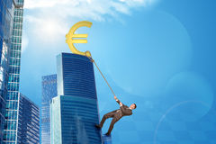Businessman climbing skyscraper with euro sign Royalty Free Stock Images