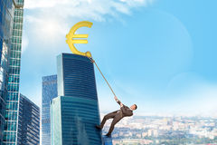 Businessman climbing skyscraper with euro sign Stock Photos