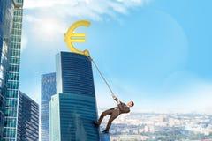 Businessman climbing skyscraper with euro sign Stock Photos