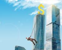 Businessman climbing skyscraper Royalty Free Stock Image