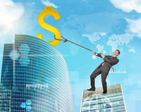 Businessman climbing skyscraper with world map. Businessman climbing skyscraper holding golden dollar sign Royalty Free Stock Photography