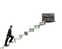 Businessman climbing spiral staircase toward treasure chest on m Stock Images